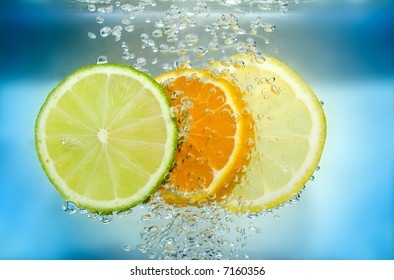 Tangerine lime and lemon slices in blue water with air bubble.