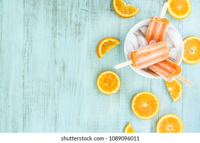 Tangerine popsicles in a bowl of ice with sliced oranges