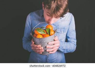 tangerines bucket in hands - vegetarian and vegan people concept