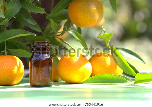 Tangerines and citrus oil in a bottle.