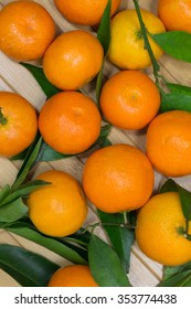 Tangerines and green leaves on the light background