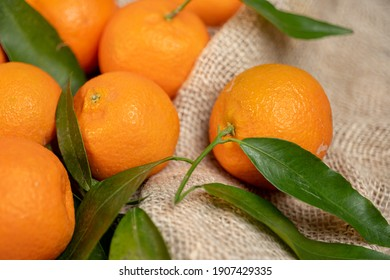 tangerines with leaves on a texture bag