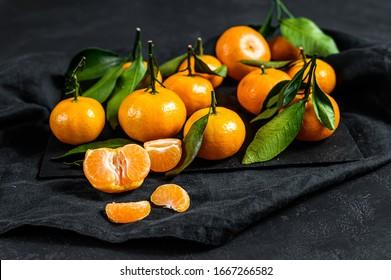 Tangerines, mandarines with leaves. Black background. Top view