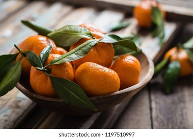Tangerines (mandarins or citrus fruits) with leaves in wooden bowl on rustic wooden background, copy space