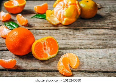 Tangerines (mandarins, clementines, citrus fruits) with leaves over rustic wooden background with copy space