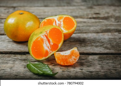 Tangerines (mandarins, clementines, citrus fruits) with leaves over rustic wooden background