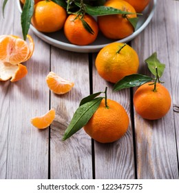 Tangerines, mandarins, fresh citrus fruits with leaves on wooden background, vitamins, healthy raw food square image