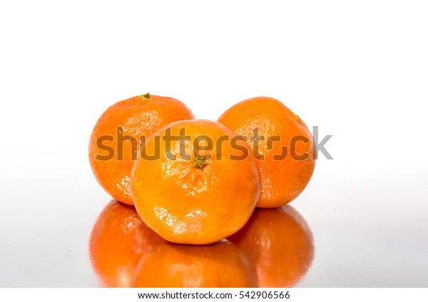 Tangerines on reflective background.