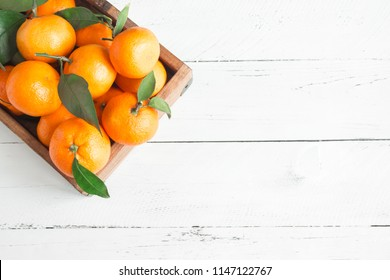 Tangerines (oranges, clementines, citrus fruits) with green leaves over white wooden background with copy space