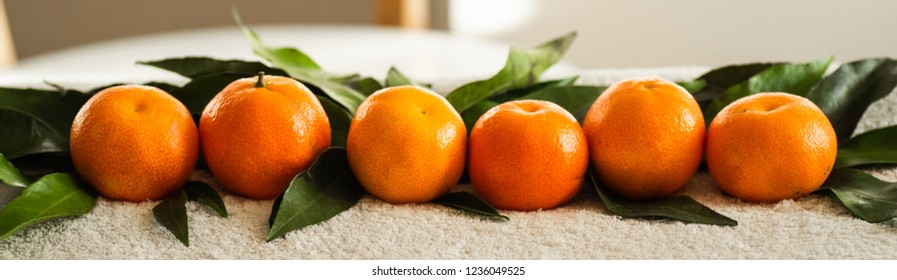 Tangerines (oranges, mandarins, clementines, citrus fruits) with leaves on white plaid, white background, copy space
