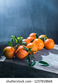 Tangerines oranges, mandarins, clementines, citrus fruits with leaves in basket over rustic wooden background, copy space