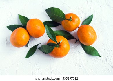 Tangerines (oranges, mandarins, clementines, citrus fruits) with leaves over rustic white stone background with copy space