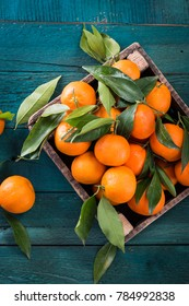 Tangerines (oranges, mandarins, clementines, citrus fruits) with leaves in basket over rustic wooden background, copy space