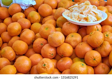 Tangerines for sale at a market with some pieces on a plate