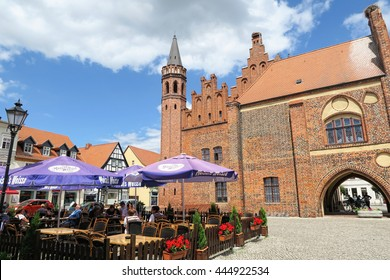 TANGERMUENDE, SAXONY-ANHALT/ GERMANY June 26 2016 Cityscape of Tangermunde (Saxony-Anhalt, Germany) with town hall and people sitting in a restaurant.