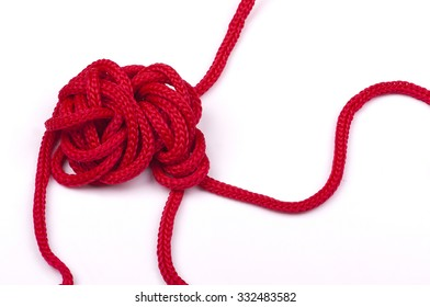a tangle of matted red rope on a white background closeup