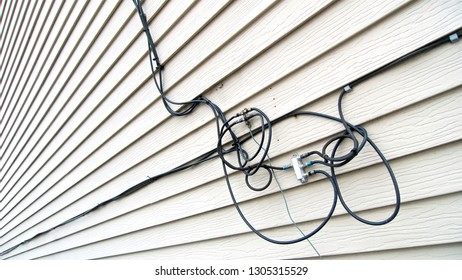 A tangle of telecommunications cables with internet, television, and phone lines installed on the siding of a house.