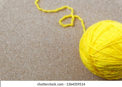 A tangle of yellow threads on a yellow cork background with a copy of the space. A wool ball is bright yellow with rasborinae disentangled thread. Needlework concept. Craft idea.