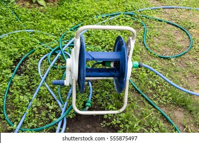 tangled garden hose with a reel on the grass