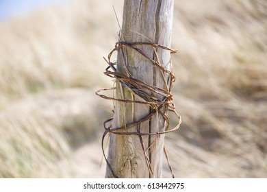 tangled metal wires on a wooden pole. The end part of a fence