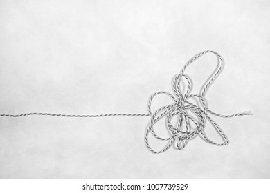 A tangled piece of string layed out on a white background.  Black and white photograph.