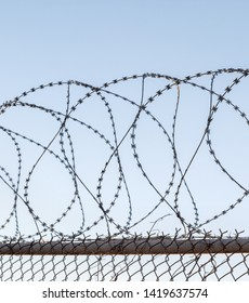 Tangled razor wire on top of a wire mesh perimeter fence, against a blue sky
