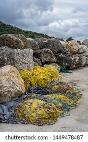 Tangled yellow fisherman fishing nets left abandoned and piled up on the shore of in Zante Island, Greece