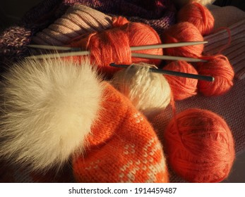 Tangles, snarls. Balls of yarn and thread, knitted clothes, knitting needles and crochet hooks. Pink, purple, red and white threads in skeins. Defocused image. Knitting and weaving as a hobby