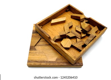 Tangram, Chinese traditional puzzle game made of different wood parts that come together in a  distinct shape, in a wooden box