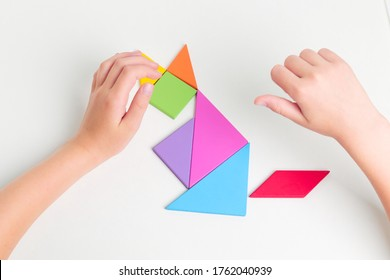 Tangram colored geometric puzzle pieces with childs hands moving pieces on white table, top view.