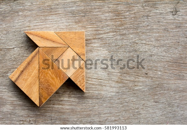Tangram puzzle in arrow shape on wooden background