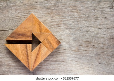 Tangram puzzle as arrow in square shape on wooden background (Concept for business direction and decision)