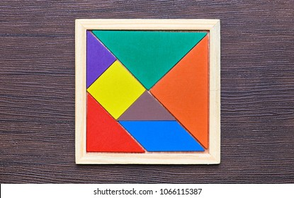 A tangram puzzle consisting of colored pieces with geometric shapes, collected in a square on a dark wooden background