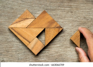 Tangram puzzle in heart shape wait to fulfill with triangle shape on wooden background