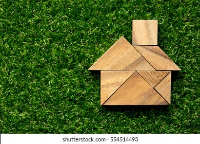 Tangram puzzle in home shape on artificial green grass background (Concept for dream home)