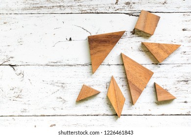 Tangram puzzle in piece wait to complete shape on old white wood background