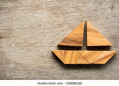 Tangram puzzle in sail boat shape on wooden background
