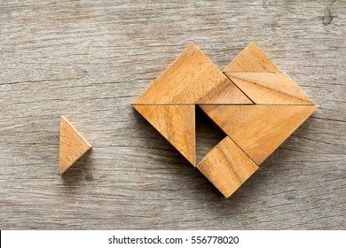 Tangram puzzle wait for fulfill to heart shape on wooden table