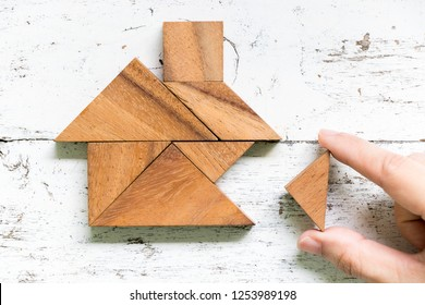Tangram puzzle wait to fulfill home shape on old white wood background (conept for build dream home, happy life, house or mortgage investment)