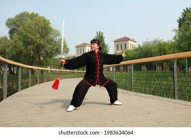 Tangshan City, Hebei Province, China - May 11, 2019: A lady in black is practicing tai chi sword in the park.