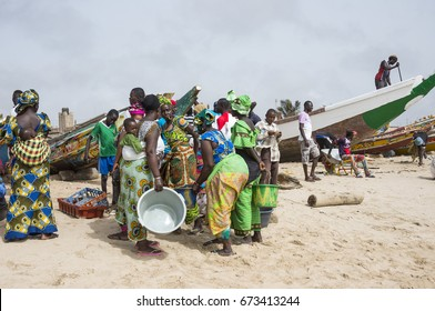 TANJI, THE GAMBIA - MAY 08, 2017: Group of women next to fishing boats, on the beach