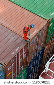 tanjung pelepas port, malaysia - september 03, 2006: a stevedore on top of a stack of containers stowed on deck of containership lt cortesia (imo 9293753)  unlocking twistlocks before discharge at ptp