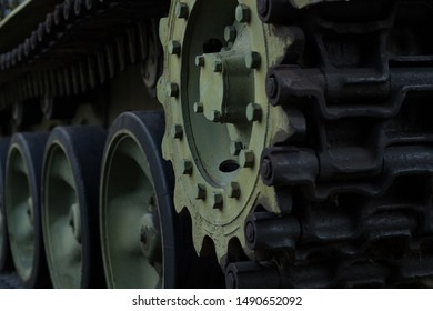 Tank caterpillar close-up. Military background image of a tank track front side view. Big powerful gear, wheels and caterpillar.