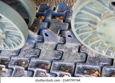 Tank caterpillars close-up. Iron caterpillars of the military heavy tank. Iron caterpillars and wheels of the military heavy tank.