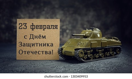 "tank and lettering congratulation ""February 23 Defender of Fatherland Day"". February 23 Holiday background. men's day of defenders in Russia, Belarus,Tajikistan, Kyrgyzstan. Tank toy on dark backdrop"