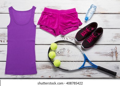 Tank top with sport shorts. Female tennis outfit on table. Tennis equipment with water bottle. Move quickly and win.