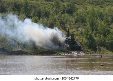 The tank training ground in Eastern Siberia.Military exercises of the tank brigade in a situation close to the combat situation.   Tanks pass under the water through the bottom of the river.