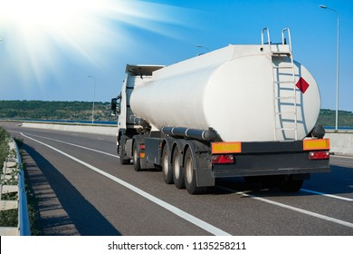 tank truck rides on highway, white blank color, rear view, one object on road