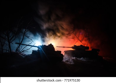Tank under the snow at night in forest at conflict zone. Silhouette of military tank during attack. War military concept idea