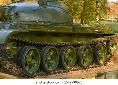 Tank wheels close-up. Iron tracks of a heavy military tank. Iron caterpillars and wheels of a military heavy tank. View of the front part of the green caterpillar of the tank standing on the ground